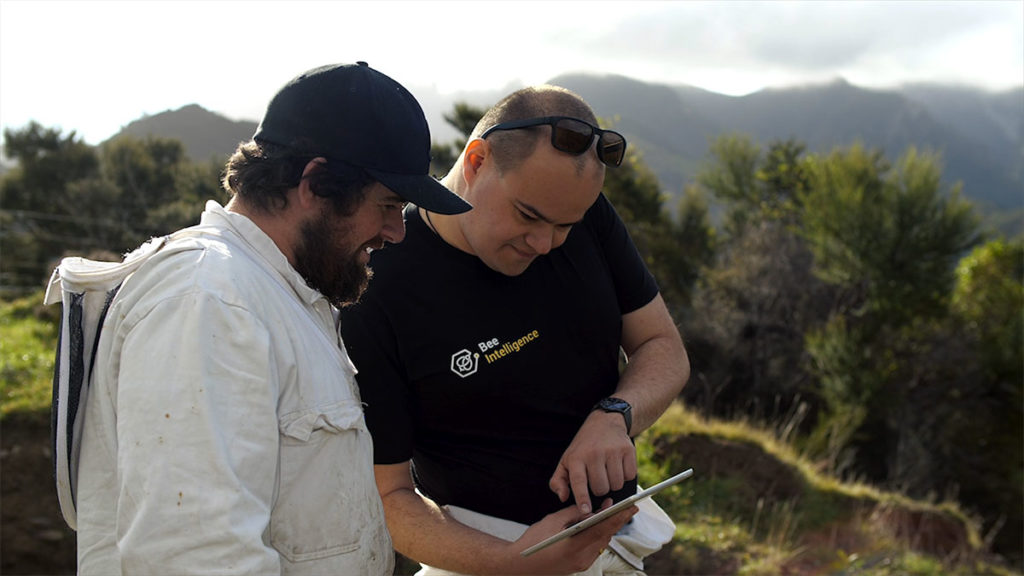 BeeApp Co-founder and CEO Erik Bast, left, out in the field with the BeeApp. Photo: Supplied.