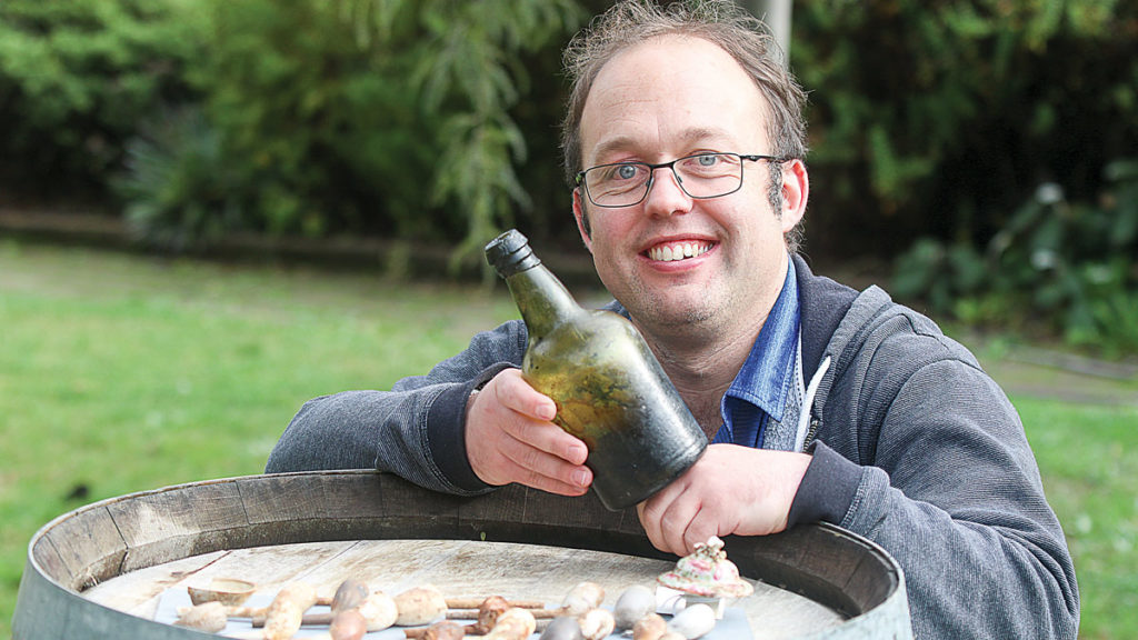 Marlborough Heritage Trust regional collections manager Logan Coote with the mystery bottle. Photo: Matt Brown.